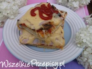 Pizza z papryką, cebulą, pieczarkami i szynką.